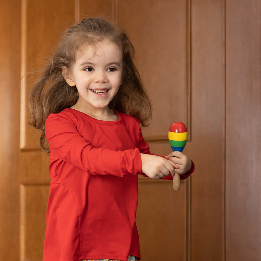 Young girl with Autism holding toy and smiling