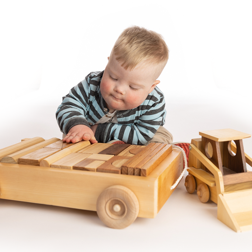 Toddler with Down syndrome playing with wooden toys