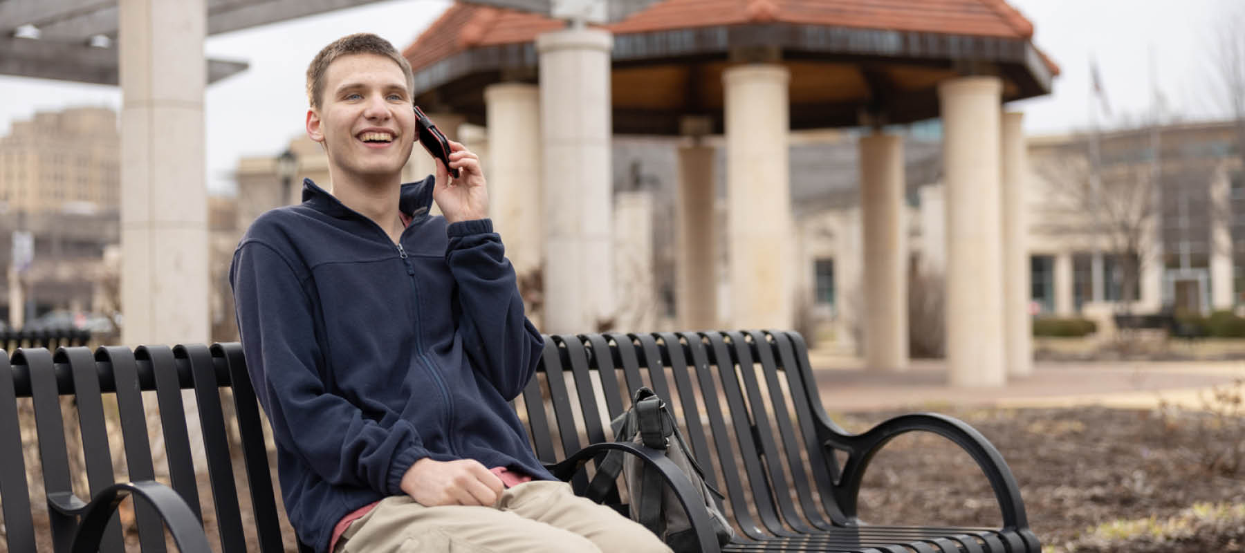 Young man with Autism sitting on bench talking on phone and smiling