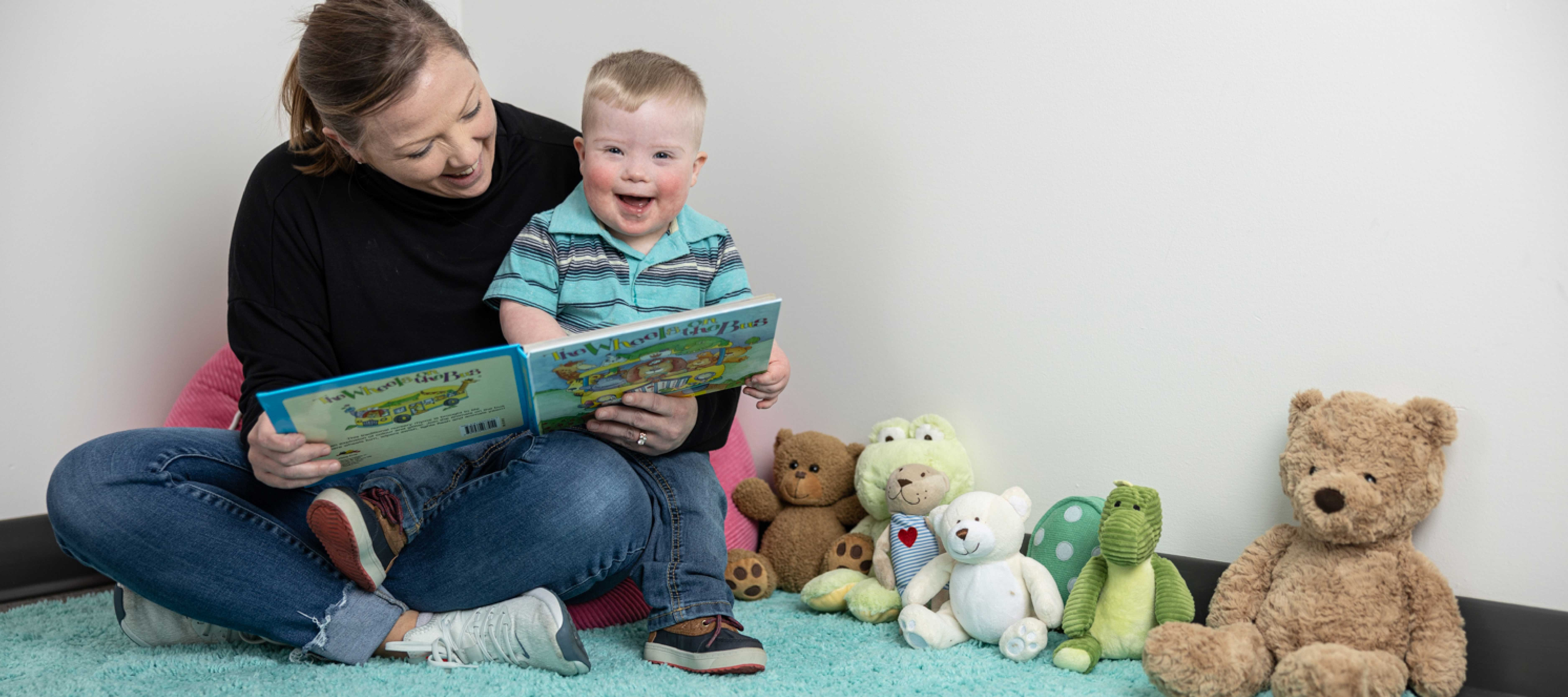 Toddler with Down syndrome on Mom's lap, smiling while she reads